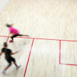 Two female squash players in fast action on a squash court (moti — Stock Photo