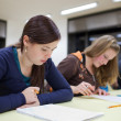 Pretty female college student sitting an exam in a classroom ful — Stock Photo #4695756