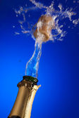 Clos-up of an uncorked champagne bottle with cork flying away on the liquid — Stock Photo