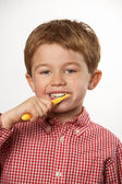 Cute young boy brushing teeth with positive expression — Stock Photo