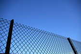 Chain link fence see blue sky — Stock Photo