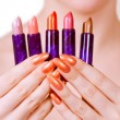 Girl holding five lipsticks — Stock Photo #4451396