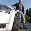 Stock Photo: Mand his sports car