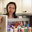 Housewife in her kitchen with apothecary cabinet — Stock Photo
