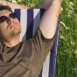 Man in meadow relaxing in deck chair - Stockfoto