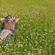 Man in meadow relaxing in deck-chair — Stock Photo
