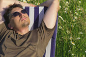 Man in meadow relaxing in deck chair — Stock Photo