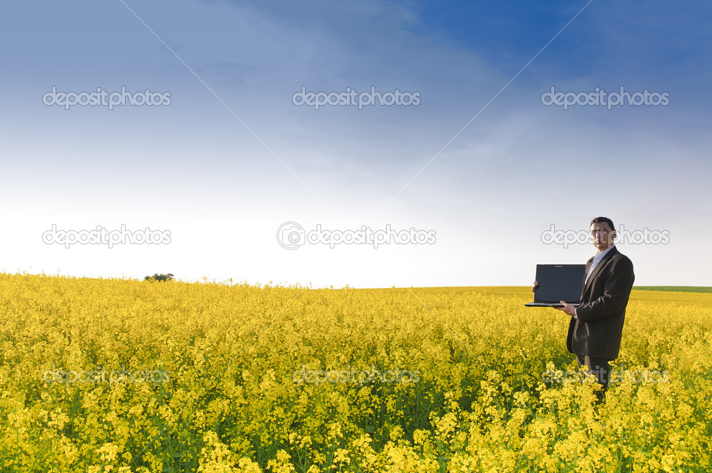 Adult manager in a suit stands with his laptop computer in a yellow flowering rape field in the evening sun. — Stock Photo #4813968