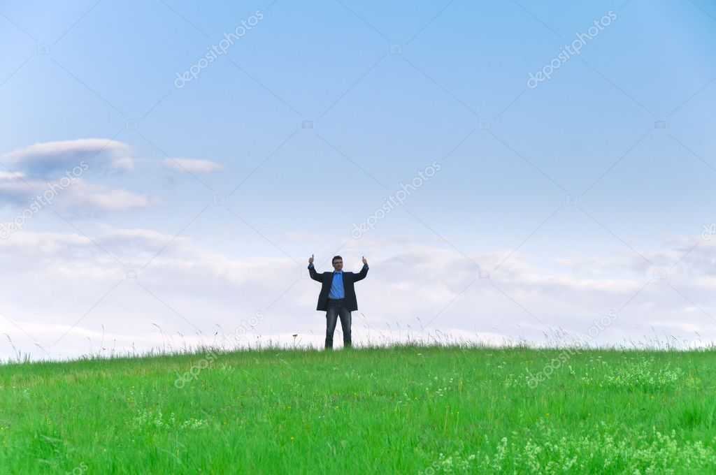Businessman in suit standing on a meadow and looks into the distance in front of clouds — Stock Photo #4815361