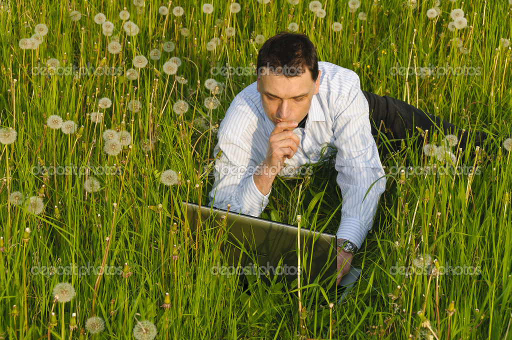 Businessman in suit standing on a meadow and looks into the distance in front of clouds — Stockfoto #4816220