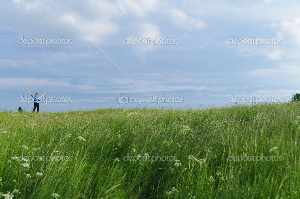 Businessman in suit standing on a meadow and looks into the distance in front of clouds — Stock Photo #4817754