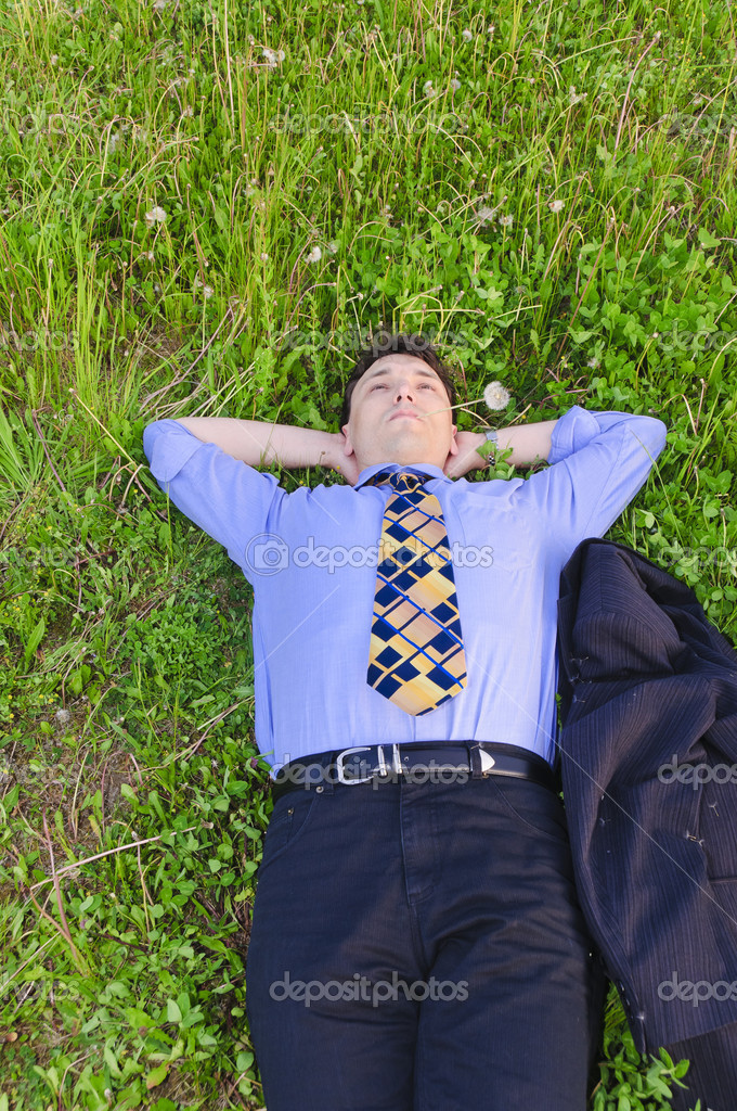 Businessman in suit is on a flowery meadow and relaxed  Stock Photo #4817911