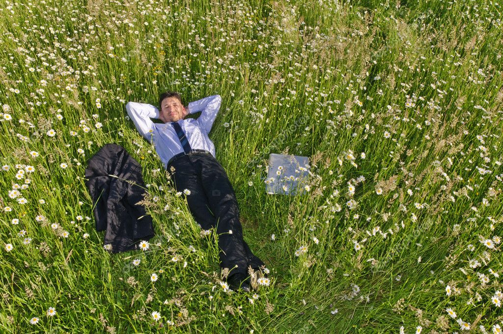 Businessman in suit is on a flowery meadow and relaxed — Stock Photo #4818448