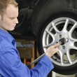 Foto de Stock  : Changing wheels in car workshop