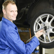 Foto Stock: Changing wheels in car workshop