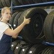 Female car mechanic with tire - Stock Photo