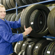 Car mechanic with tire - Stockfoto
