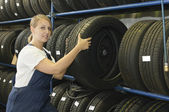 Female car mechanic with tire — Stockfoto