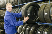 Car mechanic with tire — Stock fotografie