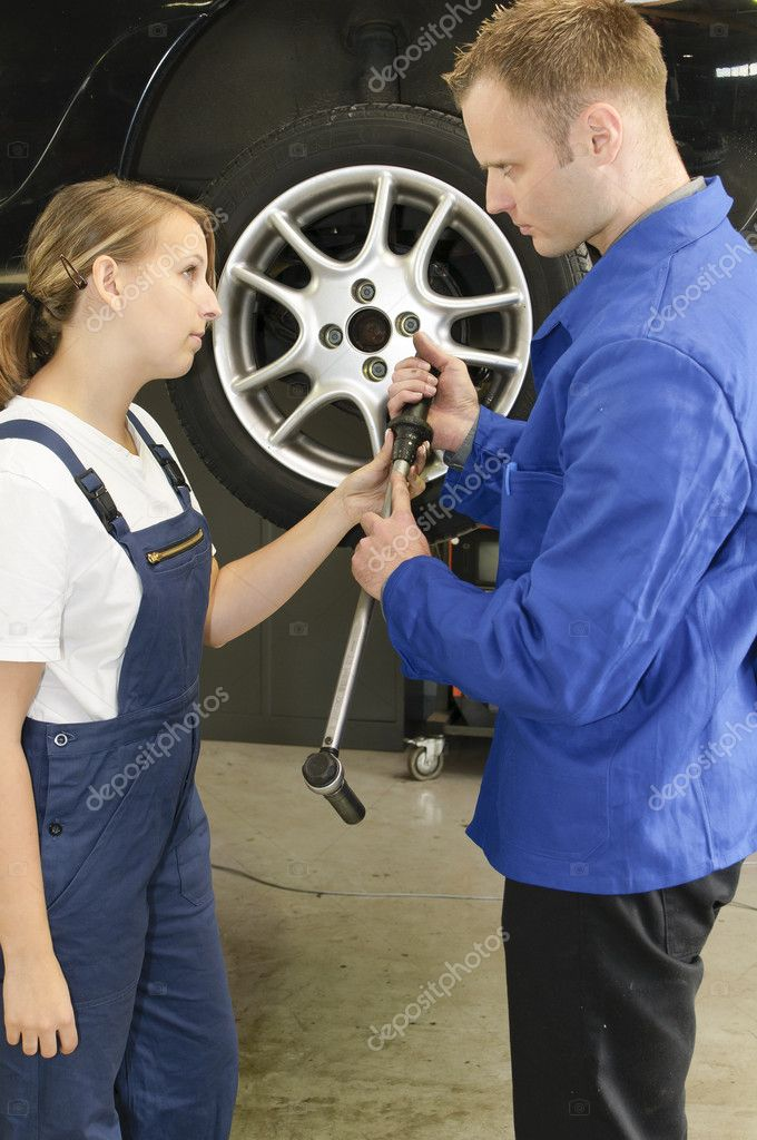 Auto mechanic shows the female trainee maintenance of the wheels in workshop in front of a car — Stock Photo #5032689