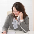 Smiling young woman on the phone at office — Stock Photo