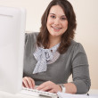Happy businesswoman sitting at office desk — Stok fotoğraf #4680180