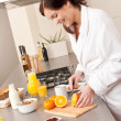 Stock Photo: Young woman in bathrobe cutting orange in kitchen
