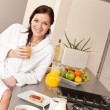 Young woman having breakfast in modern kitchen — Stock Photo