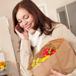 Smiling woman with mobile phone holding shopping bag — Stock Photo