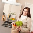 Woman holding shopping bag with grocery in kitchen — Stock Photo #4680384