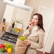 Young woman unpacking shopping bag in kitchen — Stock Photo #4680385