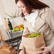 Young woman unpacking shopping bag in kitchen — Stock Photo #4680387
