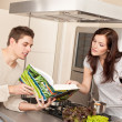 Young couple in kitchen choosing recipe from cookbook — Stock Photo