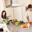 Young couple cooking in kitchen together — Stock Photo