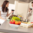 Young couple drinking red wine in kitchen — Stock Photo #4680406