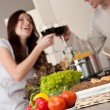 Young couple drinking red wine in kitchen — Stockfoto