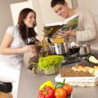 Stock Photo: Couple in kitchen choosing recipe from cookbook
