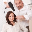 Professional hairdresser with hair dryer at salon with customer - Stock Photo