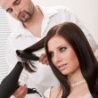 Professional hairdresser with hair dryer at salon — Stock Photo