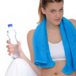 Fitness - Young sportive woman with water and towel — Stock Photo