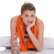 Fitness girl with orange towel — Stock Photo