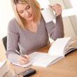 Student series - Blond girl writing homework — Stockfoto