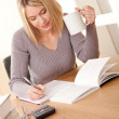 Foto de Stock  : Student series - Blond girl writing homework