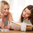 Student series - Two teenage girls reading together - Stock Photo