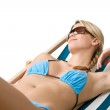 Beach - Young woman in bikini lying on deck chair — Stock Photo #4682067