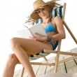 Beach - Young woman relax with book in bikini - Stock Photo