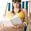 Beach - Young woman in bikini sunbathing with book - Stock Photo
