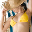 Beach - woman with straw hat in yellow bikini sunbath — Stock Photo #4682163