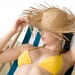 Beach - woman with straw hat in yellow bikini sunbath — Stok fotoğraf