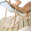 Beach - topless woman sitting on deckchair - Stock Photo